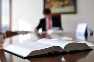 närbild av en öppen bok på ett kontorsskrivbord