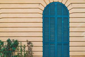 välvd dörr med blå fönsterluckor foto