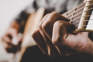 närbild av mannen som spelar gitarr foto