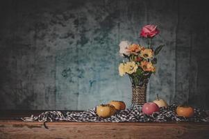 stilleben med en vas med blommor och frukt på tyg foto