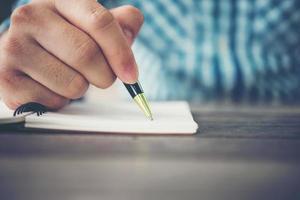 närbild av manhandhandstil i anteckningsbok med pennan foto