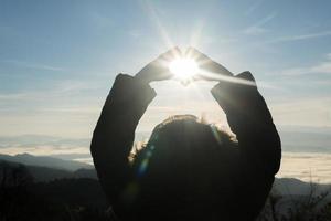 glad ung kvinna vandrare med öppna armar upp vid solnedgången