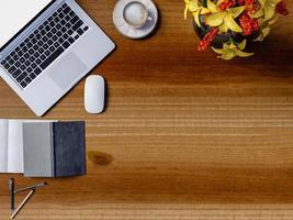 ovanifrån av ett träbord i regeringsställning med bärbar dator och kaffekopp