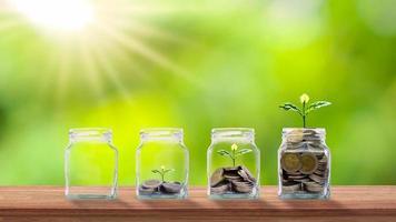 plantera träd i klara flaskor för att spara pengar på ett träbord och suddiga gröna idéer för affärstillväxt