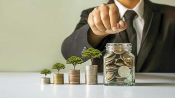 plantera ett träd på en hög med pengar och affärsman, man sparar pengar, pengar sparar idéer för framtida investeringar