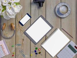 håna upp arbetsytan på bordet med anteckningsbok, surfplatta, telefon, hörlurar foto