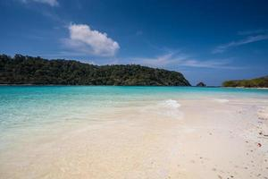 vit sandstrand med blått vatten foto