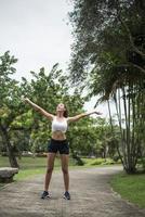 ung sportig kvinna som sträcker sig i parken foto