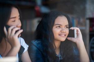 ung kvinna som använder och tittar på smarttelefonen foto