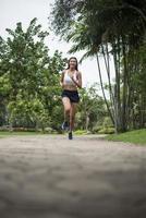 ung sportig kvinna som kör i parken foto