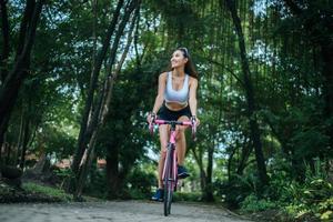 ung kvinna som cyklar i parken