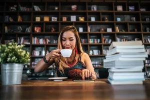 kvinna som dricker cappuccino och läser en bok