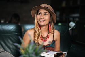 ung kvinna som läser en bok på ett kafé