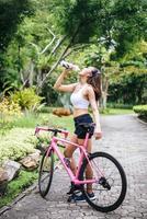 porträtt av ung kvinna med en rosa cykel i parken foto
