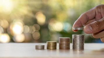 mänskliga händer lägger silvermynt i mynt, ekonomiska begrepp och affärstillväxt foto