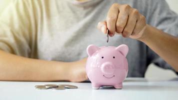 kvinnor lägger silvermynt i smågrisar för att spara pengar och spara pengar för framtida investeringar. ekonomiskt koncept foto