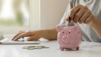 kvinnor lägger in mynt i smågrisar för att spara pengar och spara pengar för framtida investeringar i finansiella och investeringsidéer foto