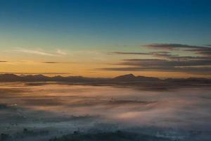 Flygfoto över berg och dimma vid solnedgången foto