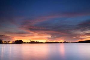 dramatisk solnedgångshimmel över vatten foto