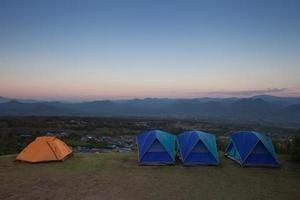 tält på ett berg ovanför en stad foto