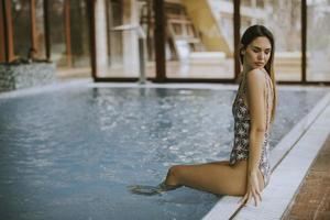 vacker ung kvinna sitter vid poolen foto