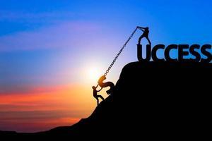framgång och lagarbete koncept, silhuett av två personer som drar kedjor upp ett berg