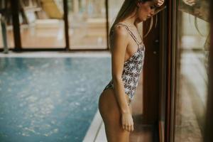 vacker ung kvinna som står vid fönstret vid poolen