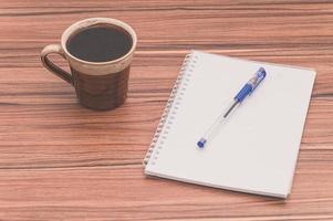 kaffemugg och tom anteckningsbok på bordet foto