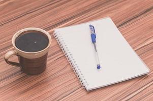 kaffemugg och anteckningsbok på bordet foto