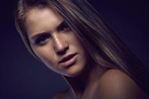 skönhetsporträtt av en ung sexig kvinna mot en mörkblå bakgrund