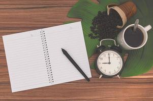 anteckningsbok och kaffemuggar på skrivbordet foto