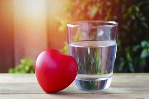 rött hjärta med glas dricksvatten foto
