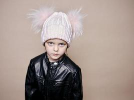 porträtt av en vacker liten flicka med en ullhatt och en läderjacka