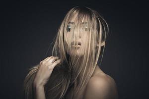 skönhetsporträtt av en ung sexig kvinna mot en blå bakgrund foto