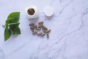 örtmedicin i kapslar på marmor foto