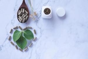 örtmedicin i kapslar på träsked på vit marmor foto