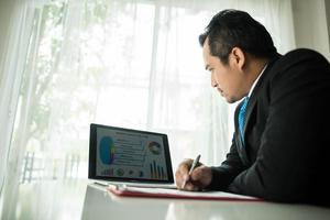ung affärsman som arbetar med bärbara datorn på kontoret