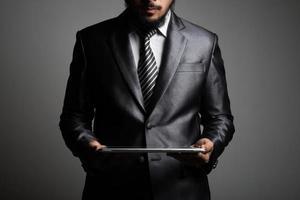 stilig affärsman som tittar på en tablett, isolerad på svart bakgrund
