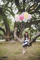 liten söt asiatisk flicka sitter på trädgren med färgglada ballonger
