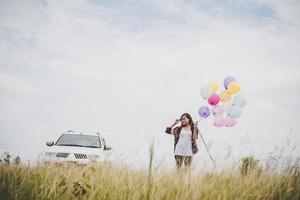 vacker ung hipster kvinna med färgglada ballonger utomhus