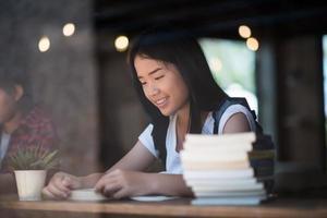 ung kvinna som läser bok sitter inomhus i ett stadscafé foto