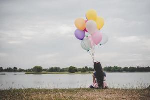 liten flicka som leker med ballonger på ängfältet