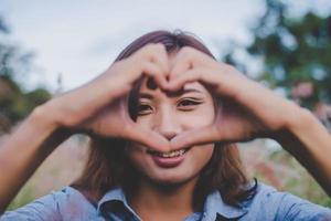 vacker kvinna ler mot kameran och gör hjärta form med händerna foto