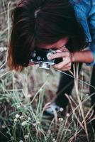 glad ung hipster kvinna med vintage kamera i fält
