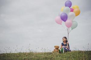 liten flicka som leker med ballonger på ängfältet foto