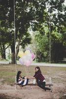 mamma med dotter som sitter på gunga med färgglada ballonger