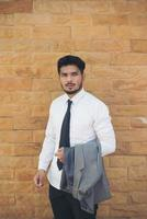 ung affärsman som rymmer en kostym mot tegelväggen