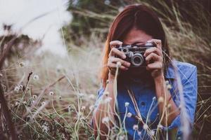 glad ung hipster kvinna med vintage kamera i fält foto