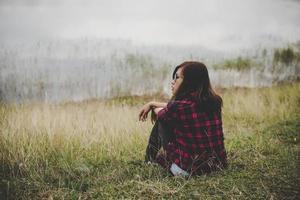 ung hipsterkvinnasammanträde på gräs nära en sjö foto
