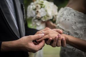 närbild av brudgummen sätta ringen på bruden foto